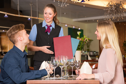 Waitress in restaurant presenting the menu to two guests